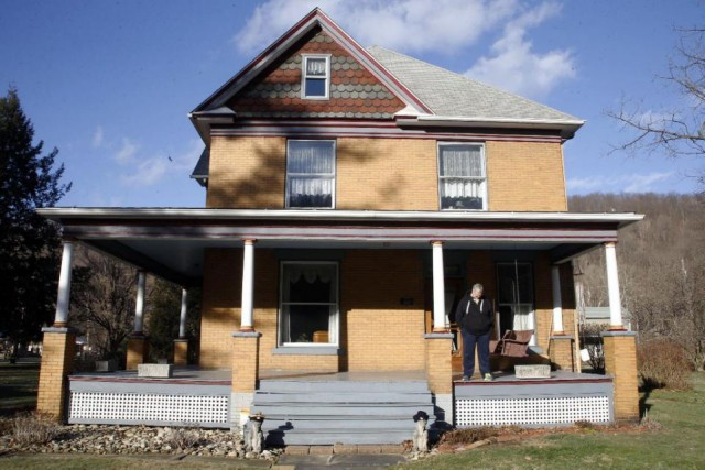 "Scott Lloyd stands on the front porch of his home which is the house used as the home of psychotic killer Buffalo Bill in the 1991 film ""The Silence of the Lambs"" on Monday, Jan. 11, 2016 in Perryopolis, Pa. Scott and Barbara Lloyd listed the house for sale last summer, but they've dropped the asking price from $300,000 to $250,000. The three-story Victorian was the second-most clicked home on Realtor.com last year, but no serious buyers. (AP Photo/Keith Srakocic)"